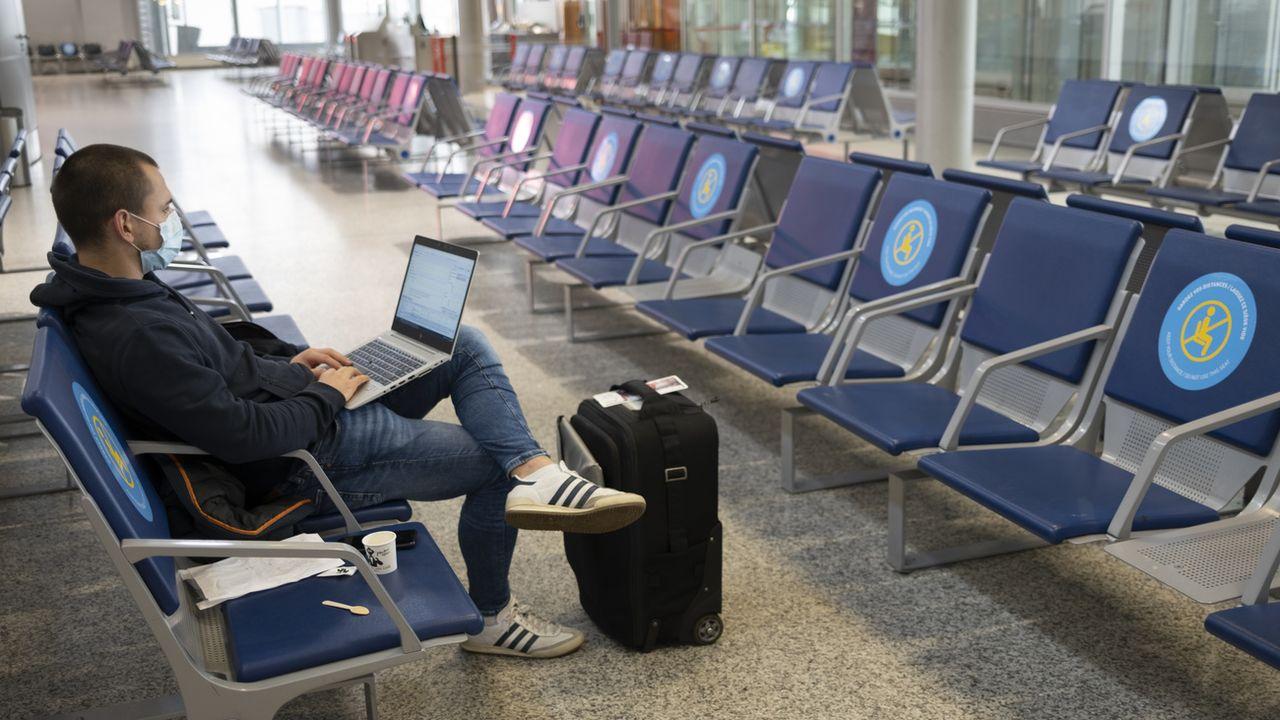 Un homme attend dans une salle d'embarquement de l'aéroport de Genève, le 10 novembre 2020. [Laurent Gillieron - Keystone]