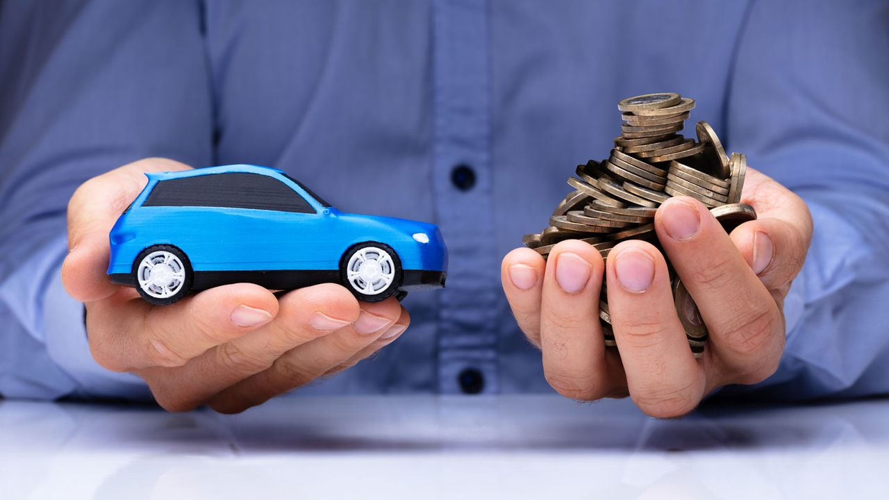 Gros plan sur deux mains qui tiennent une voiture miniature et de l'argent. [AndreyPopov - Depositphotos]