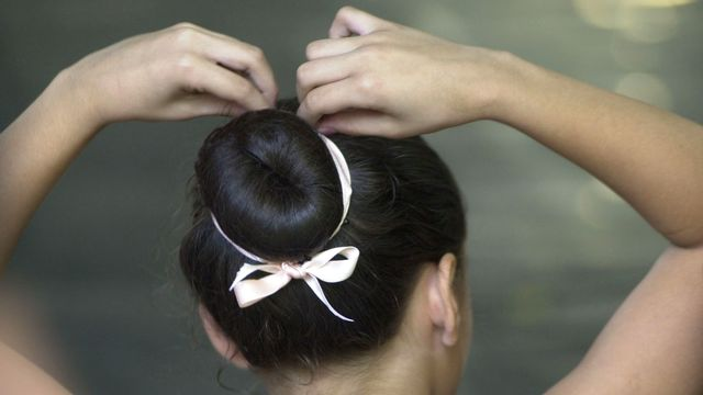 Une jeune ballerine retouche sa coiffure (image d'illustration). [Leslie Mazoch - Keystone/AP Photo]