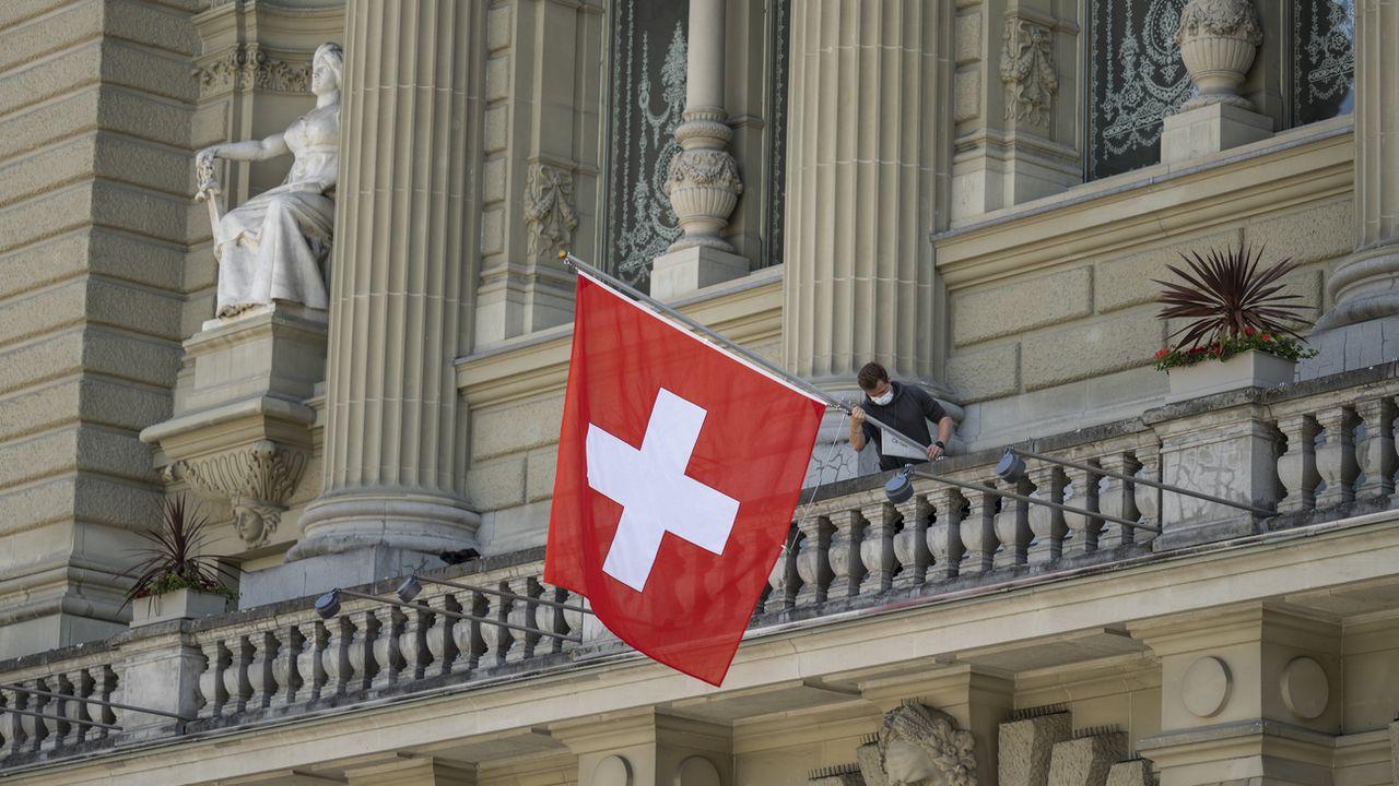 Un collaborateur du Parlement fédéral accroche un drapeau au balcon du Palais fédéral au début de de la session d'été le 31 mai 2021. [Alessandro della Valle - Keystone]