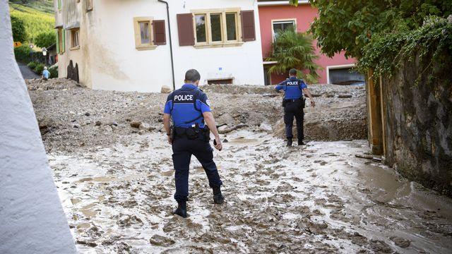 Des policiers dans la rue recouverte du boue à Cressier. [Laurent Gillieron - Keystone]