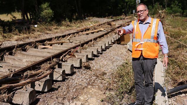 Un responsable de la Deutsche Bahn montre les dégâts sur une ligne en Rhénanie-du-Nord-Westphalie. [Oliver Berg - DPA/Keystone]
