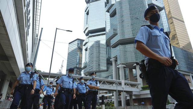 Forces de police devant la tribunal où le jeune homme a été condamné à Hong Kong, 27.07.2021. [Vincent Yu - AP/Keystone]