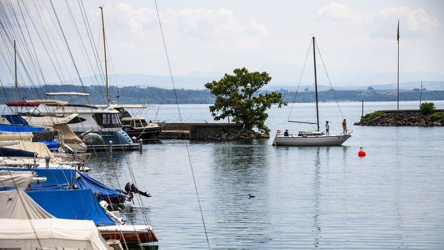 Un bateau sort du port Nid-du-Cro sur le lac de Neuchâtel. [Jean-Christophe Bott - Keystone]