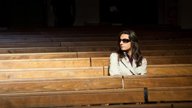 Femme seule banc d'église [Antonio Gravante - Depositphotos]