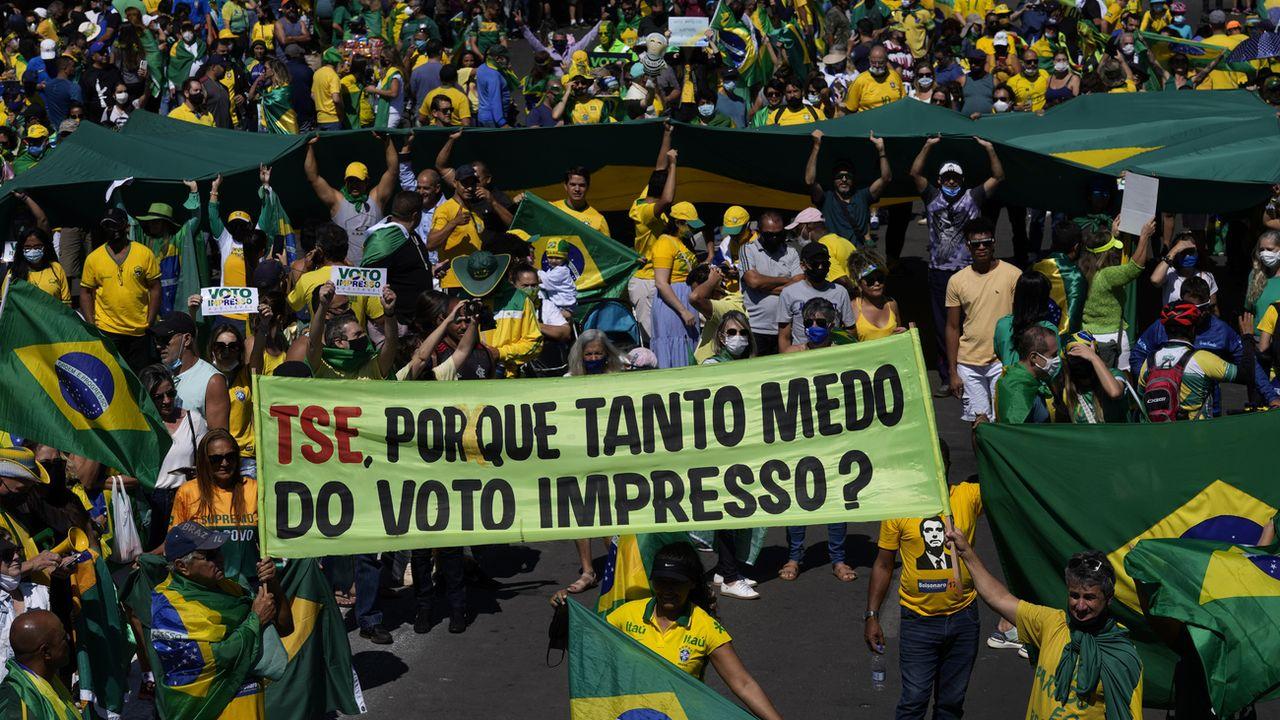 """Des manifestants pro-Bolsonaro tiennent une banderole """"TSE, pourquoi être si effrayé par les bulletins imprimés?"""". [Eraldo Peres - AP Photo]"""
