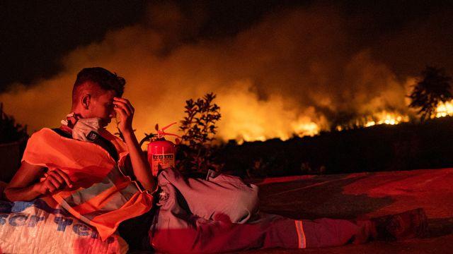Un secouriste prend une pause alors que les flammes font rage dans la province de Mugla, en Turquie. [Yasin Akgul - AFP]