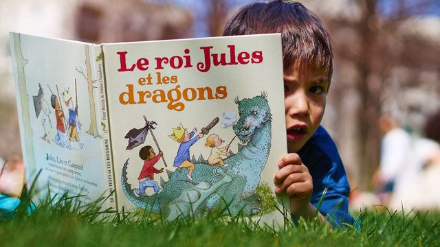 Un enfant lisant un livre dans un parc. [Godong/Bsip - afp]