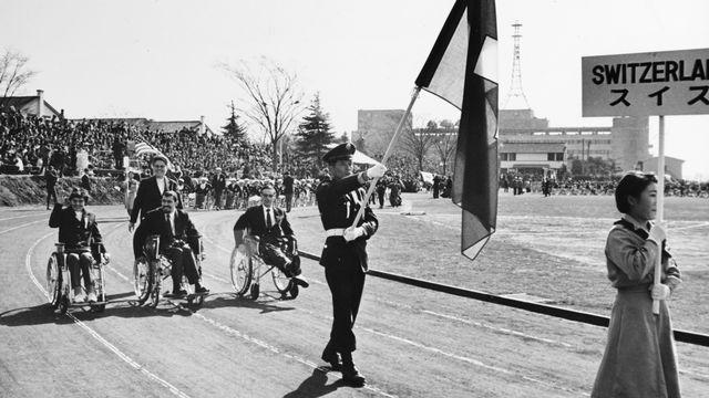 La délégation suisse lors de la cérémonie d'ouverture des Jeux paralympiques de Tokyo en 1964. [KEYSTONE/Str]