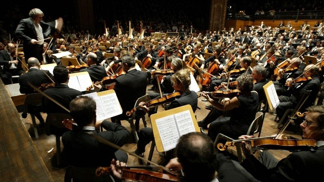 """Le chef d'orchestre Alain Lombard (G) dirige le """"grand orchestre des musiciens de France"""", le 15 novembre 2004 à la Halle aux Grains de Toulouse. [Georges Gobet - AFP]"""