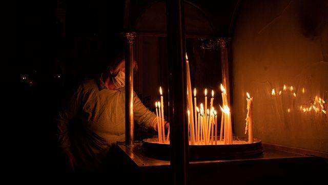 Une femme allume un cierge dans une église. [Maria Chourdari / NurPhoto - AFP]