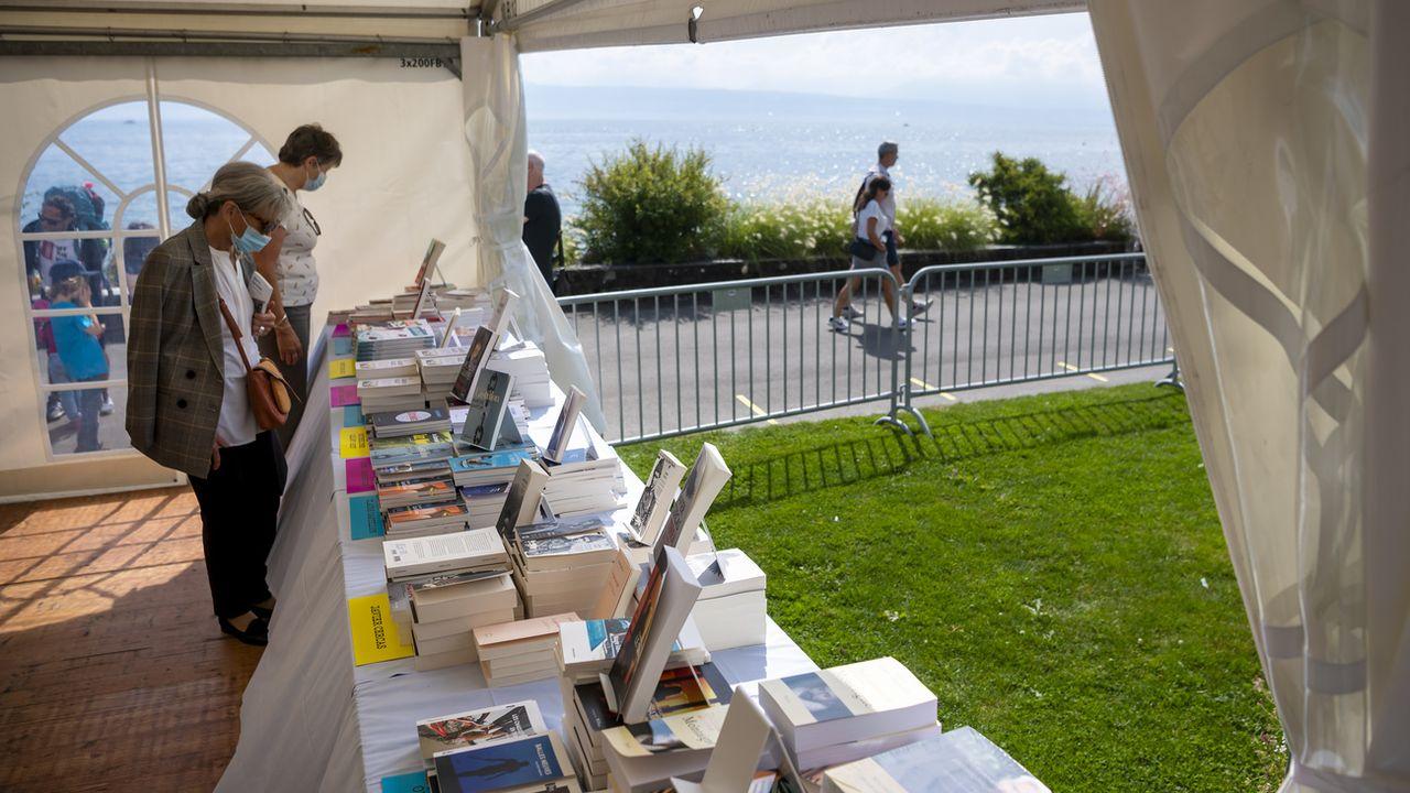 """Des personnes regardent des livres sous une tente lors de la 12eme édition du """"Livre sur les quais"""", le 4 septembre 2021. [Jean-Christophe Bott - Keystone]"""