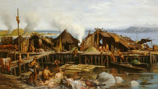 Vision idéalisée d'un village lacustre, peinte par Rodolphe-Auguste Bachelin en 1867. Contrairement à ce que l'on croyait à l'époque de ce tableau, les habitations n'étaient pas installées sur l'eau en permanence mais bâties sur la rive, sur des îles ou sur des sols marécageux, selon les saisons. [Musée national suisse]