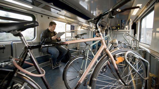 Un homme voyage dans le compartiment destiné au transport des vélos dans un train CFF. [Gaetan Bally - Keystone]
