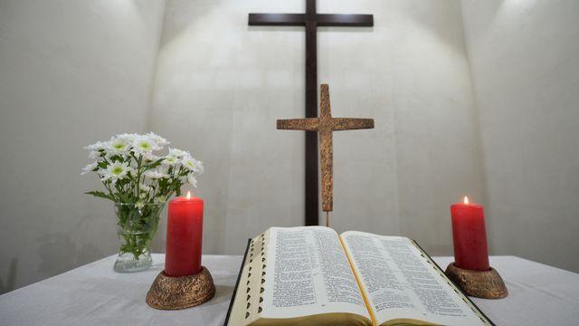 Croix, bible et bougies. [Pavel Lisitsyn / Sputnik - AFP]