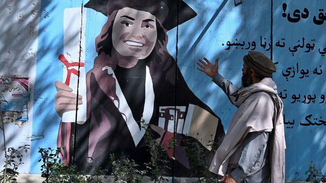 Jeudi 9 septembre: à Kaboul, un homme gesticule face à une peinture murale montrant une jeune femme diplômée. [Wakil Kohsar - AFP]