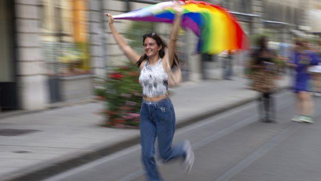Une personne arbore le drapeau LGBT+ dans une rue de Genève, à l'occasion de la Marche des fiertés, le 11 septembre 2021. [Salvatore Di Nolfi - Keystone]