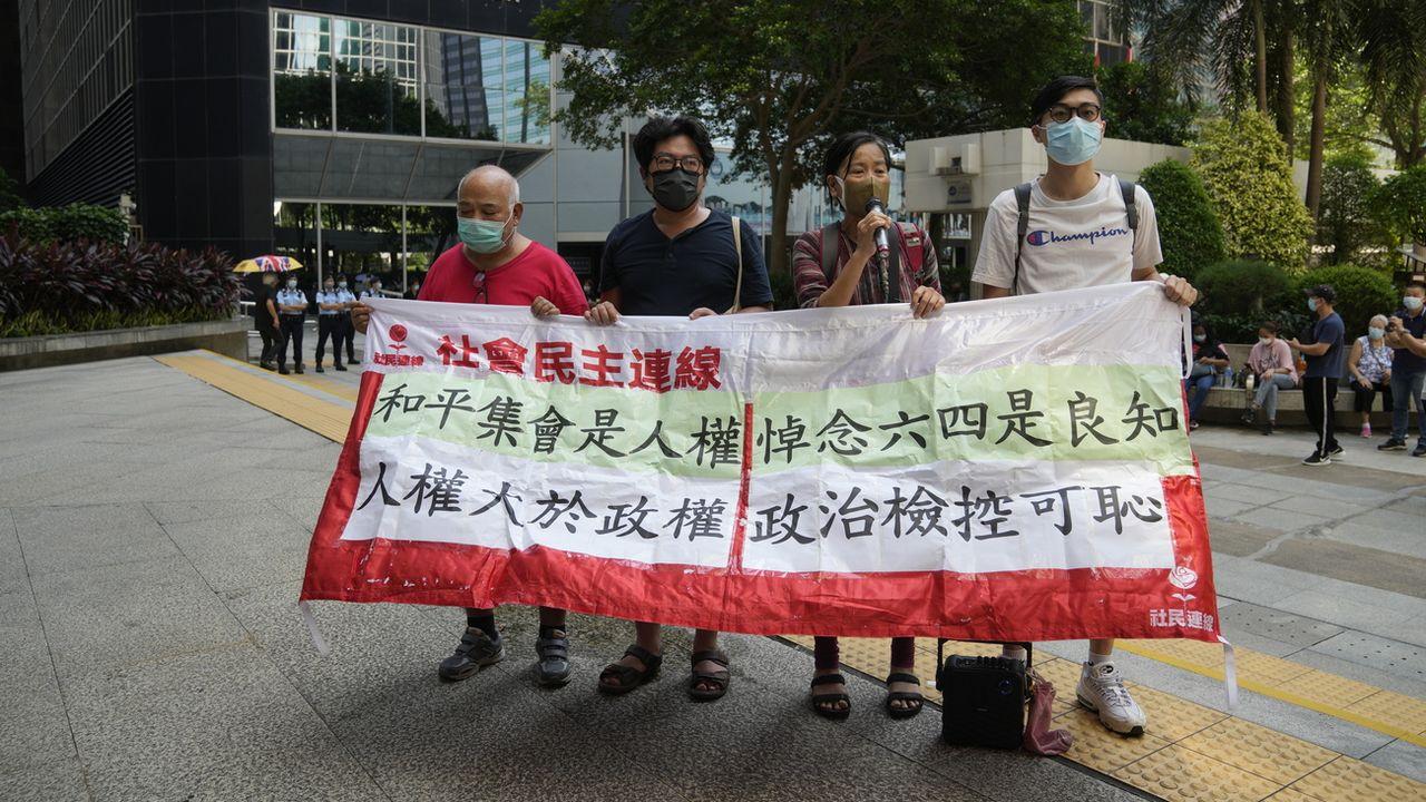 Des militants pro-démocratie protestent devant un tribunal de Hong Kong avec une banderole, le 15 septembre 2021. [Kin Cheung / AP Photo - KEYSTONE]