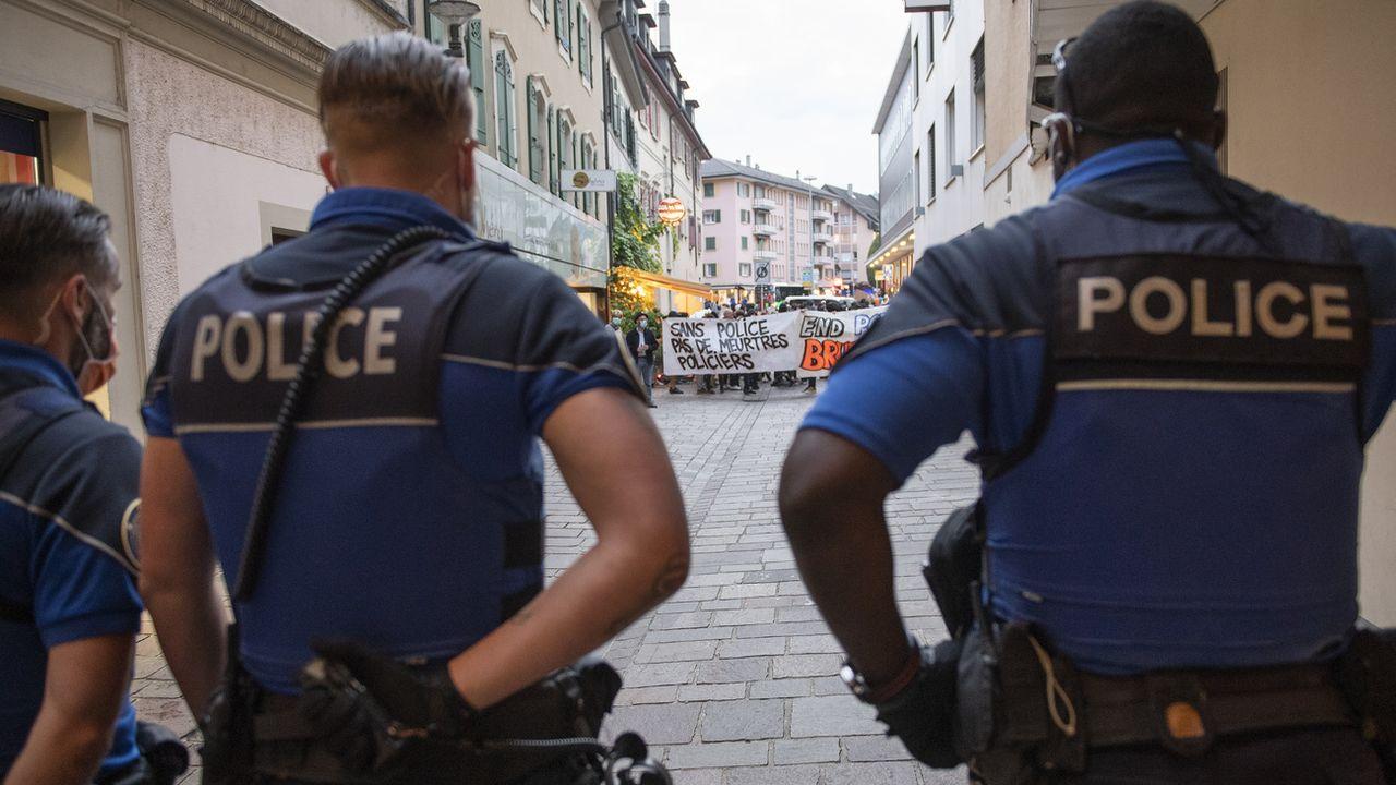 Trois policiers sont vus de dos et font face à la manifestation contre les violences policières à Morges. [Jean-Guy Python - Keystone]