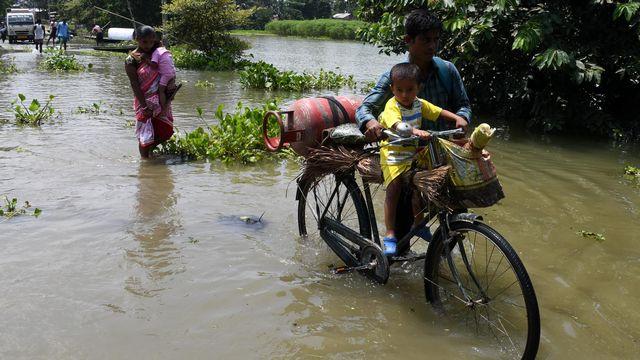 Des villageoises et des villageois s'extraient des eaux dans le district de Morigaon, dans l'Etat d'Assam. [Anuwar Hazarika - NurPhoto via AFP]