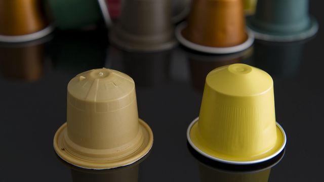 Une capsule de café biodégradable Ethical Coffee Company (à gauche) à côté d'une capsule de café Nespresso (à droite). [Jean-Christophe Bott - Keystone]