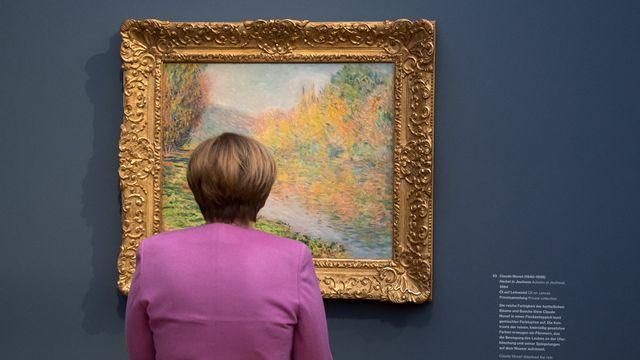 La chancelière allemande Angela Merkel devant un tableau de Claude Monet lors de l'inauguration du Musée Barberini à Potsdam près de Berlin en janvier 2017. [POOL / AFP]