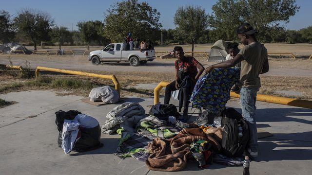 Un groupe de migrants haïtiens attendent leur transfert vers le Mexique, le 24 septembre 2021. [Felix Marquez - Keystone]