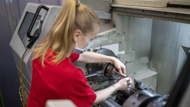 Une apprentie monte une pièce dans une machine, le 15 avril 2021 dans l'atelier de mécanique de la LBB à Bâle. [Christian Beutler - Keystone]