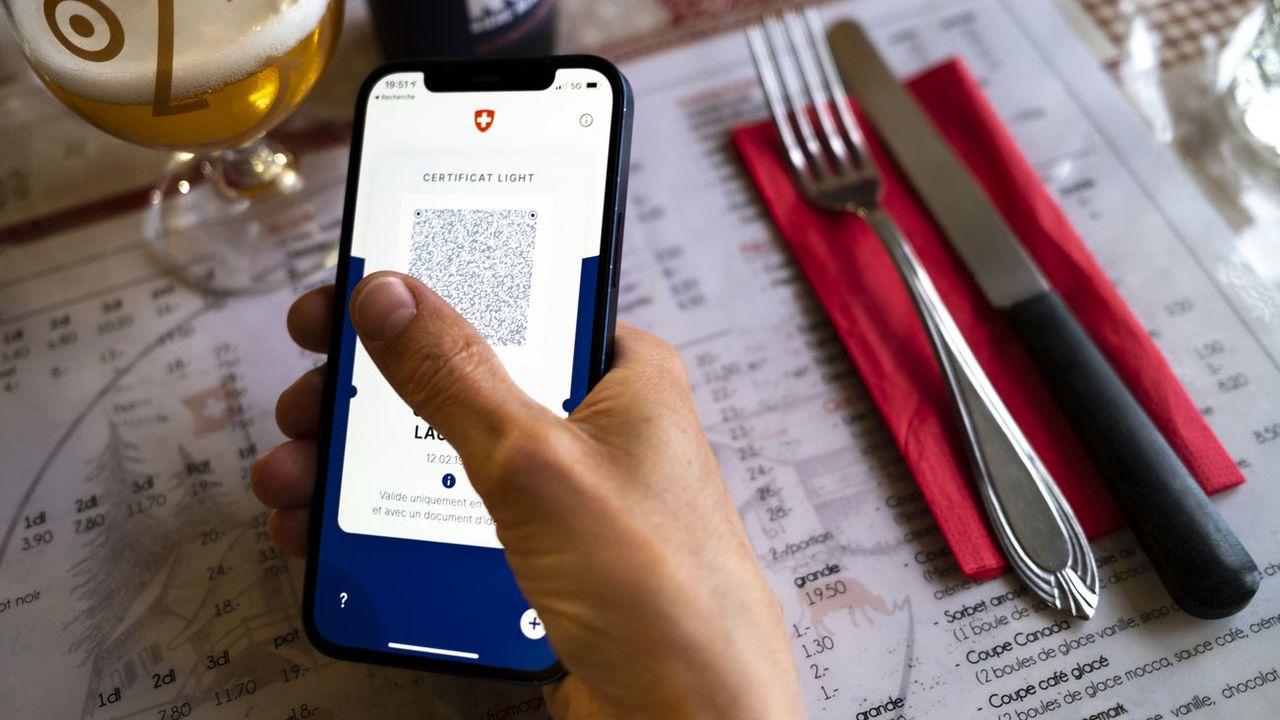 Une personne tient dans sa main un smartphone affichant un certificat Covid dans un restaurant. [Laurent Gillieron - Keystone]