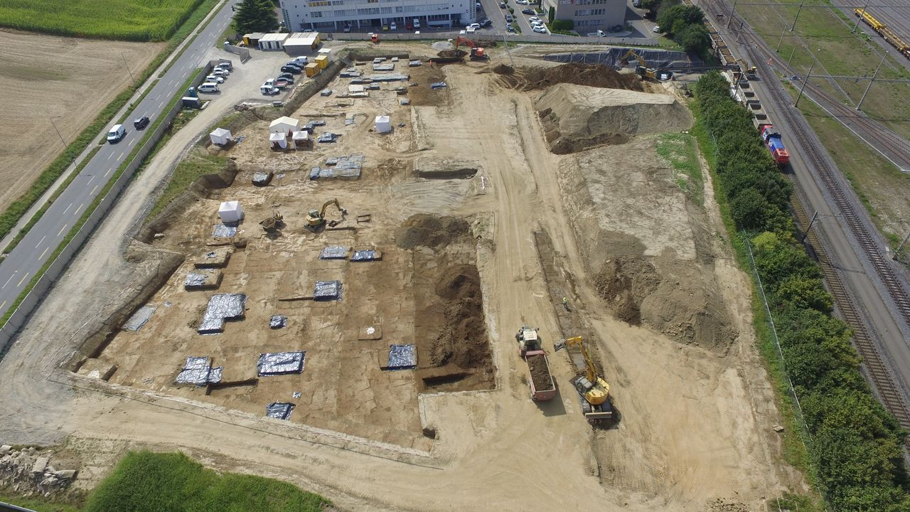 : Denges, Le Trési: vue aérienne du chantier réalisée par drone le 3 septembre 2021 (en direction de l'ouest). Les secteurs où se trouvent des sépultures à fouiller sont signalés par des bâches plastiques noires. Les tentent indiquent les tombes en cours de fouille.  [Y.Trezzi - Archeodunum SA]