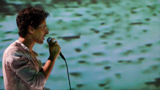 """Le comédien Mounir Margoum dans la pièce """"Contre Enquêtes"""" de Kamel Daoud, mise en scène par Nicolas Stemann. [Philippe Weissbrodt/Théâtre de Vidy]"""