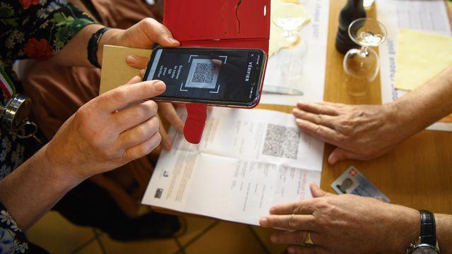Une serveuse vérifie un certificat Covid dans un restaurant lausannois, le 13 septembre 2021. [Laurent Gillieron - Keystone]