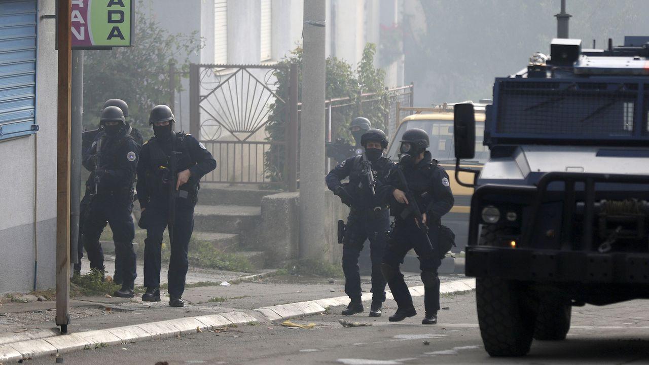 Des policiers kosovars gardent une rue de la ville de Mitrovica, le 13 octobre 2021. [Bojan Slavkovic - KEYSTONE]