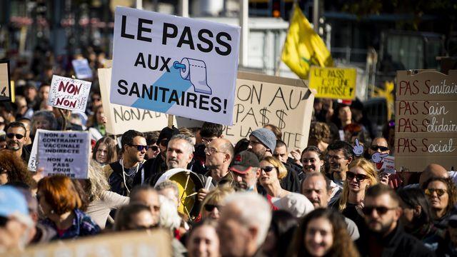 """Des personnes manifestent lors d'un rassemblement """"Non au pass sanitaire et à la restriction de nos libertés"""" le samedi 16 octobre 2021 a Lausanne.  [Jean-Christophe Bott - Keystone]"""