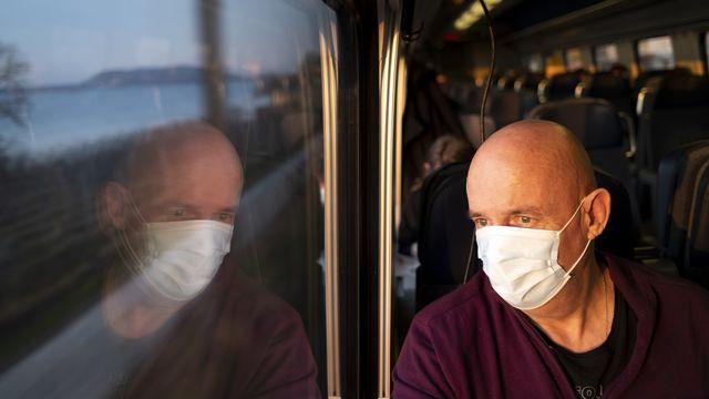 Un homme masqué dans un train. [Laurent Gillieron - Keystone]