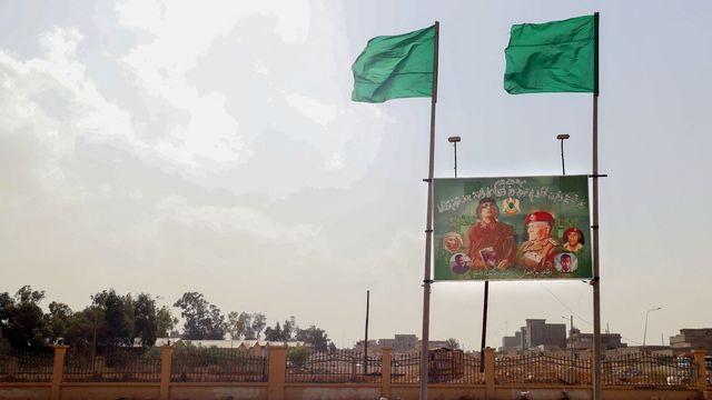 Un panneau d'affichage faisant l'éloge du leader assassiné Mouammar Kadhafi et un drapeau de l'ère Kadhafi sont visibles dans la ville de Bani Walid, le 14 octobre 2021. [Mahmud Turkia - AFP]
