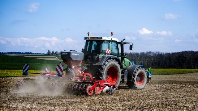Un tracteur dans la campagne vaudoise. [Jean-Christophe Bott - Keystone]