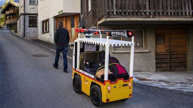 """Vendredi 22 octobre: """"Robi"""" le robot à bagages circule à Saas Fee (VS) après avoir été présenté à la presse. Il doit permettre de faciliter le déplacement des touristes avec leurs bagages dans la station. [Jean-Christophe Bott - Keystone]"""